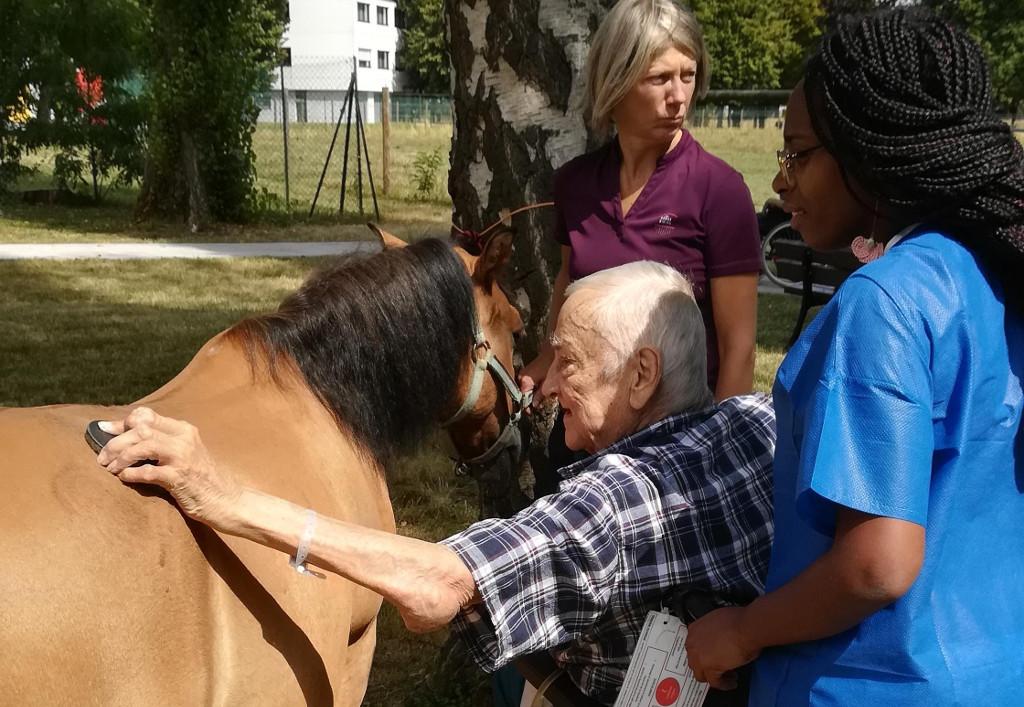 Patient et soignante pendant une séance d'équithérapie à Sainte-Marie